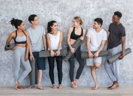 Photo for Healthy Lifestyle Concept. Group of sporty people with yoga mats resting after class near grey wall in fitness studio - Royalty Free Image
