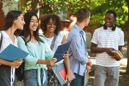 Photo pour Portrait d'étudiants internationaux souriants debout à l'extérieur à la cour du campus après les cours - image libre de droit