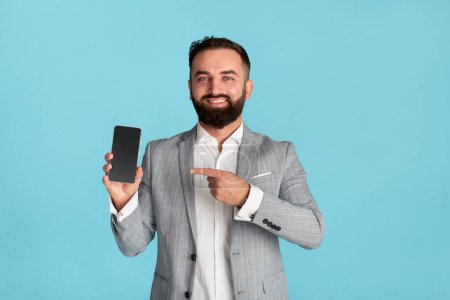 Photo pour Heureux employé de bureau pointant vers le téléphone portable avec écran blanc sur fond bleu, espace pour la conception - image libre de droit