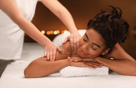 Photo pour Jeune femme noire se faire masser par une thérapeute féminine au spa - image libre de droit