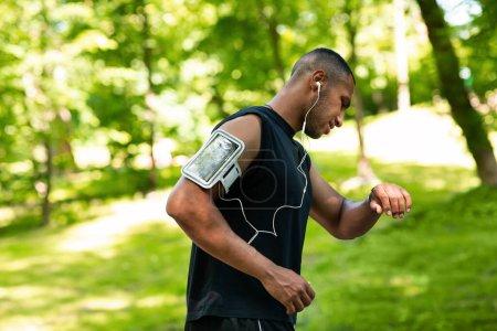 Photo pour Vue latérale du joggeur afro-américain vérifiant sa montre intelligente ou son tracker de fitness pendant la course matinale au parc - image libre de droit