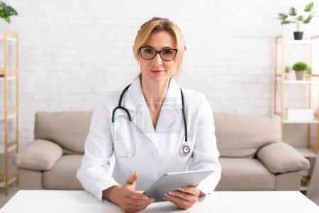Photo pour Conférence en ligne depuis la maison. Femme médecin sérieux dans les lunettes et manteau blanc avec tablette dans les mains à la table dans le salon intérieur - image libre de droit