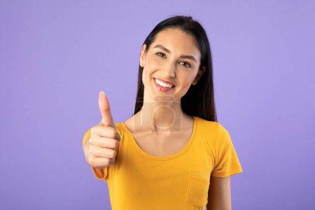 Photo pour Ça me plaît. Fille gaie montrant pouces vers le haut et largement souriant, isolé sur le mur violet pastel studio, copyspace - image libre de droit