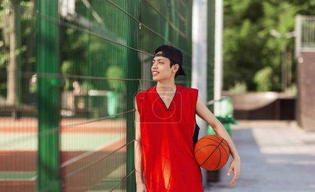 Photo pour Joueur de basket-ball asiatique millénaire avec balle debout près de la clôture à l'arène sportive extérieure, panorama - image libre de droit