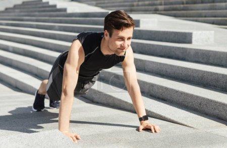 Photo pour Entraînement de force dans la rue. Jeune homme en tenue de sport faisant des pompes dans les escaliers de la ville, espace libre - image libre de droit