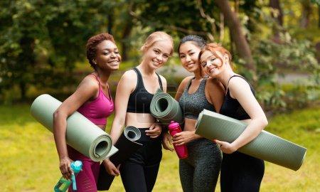 Photo pour Portrait de diverses filles avec tapis de yoga avant leur cours de sport au parc, panorama - image libre de droit