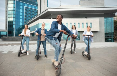 Photo for Youth Concept. Portrait of active african american guy driving stand-up scooters in urban area with his friends, full length - Royalty Free Image