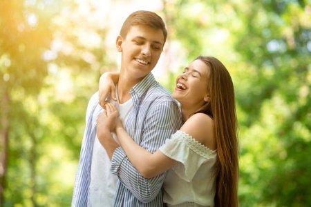 Photo pour Jolie jeune fille riant et embrassant son beau petit ami au parc d'été - image libre de droit