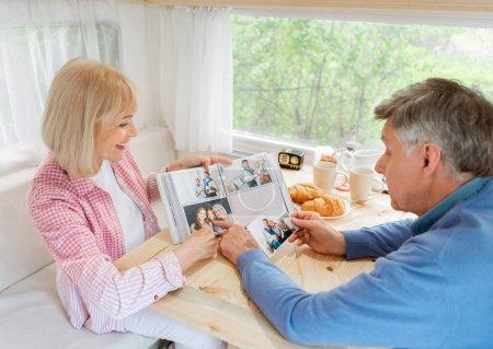 Photo pour Homme âgé et sa femme regardant à travers l'album photo de famille à l'intérieur de leur camping-car - image libre de droit