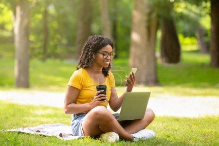 Photo pour Cool fille noire avec café, smartphone et ordinateur portable étudier en ligne au parc vert d'été - image libre de droit