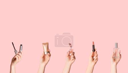 Photo pour Les mains des femmes tenant divers produits cosmétiques sur fond rose, espace vide. Collage créatif - image libre de droit