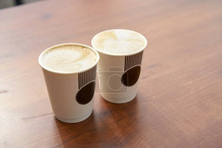 close-up view of two paper cups of coffee on table