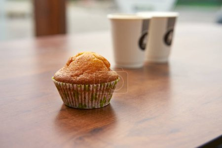 close-up view of tasty muffin on table and two paper cups of coffee on background