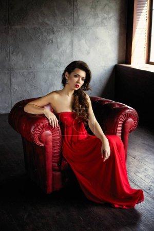 Foto de Hermosa mujer morena joven en elegante vestido rojo posando - Imagen libre de derechos