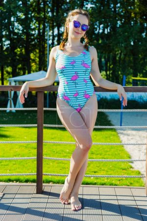 Attractive young woman in swimsuit with cute flamingos posing