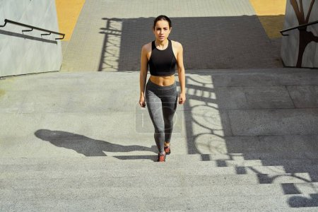 sportive young brunette woman walking on stairs