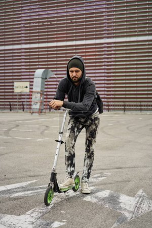Photo for Stylish young bearded man with kick scooter posing - Royalty Free Image