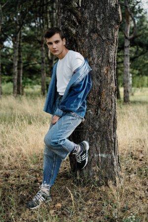 Photo pour Beau jeune gars dans casual denim vêtements posant à l'extérieur - image libre de droit