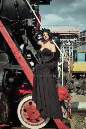 Photo for Beautiful  woman in black dress  posing  near old  locomotive  train  on station platform - Royalty Free Image