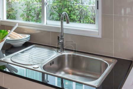 Modern sink in modern kitchen room on top counter,...