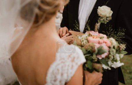 Photo pour Le marié met l'alliance sur la mariée. L'image a été prise sur l'épaule d'une mariée sans les visages du couple. Focus sur les mains des jeunes mariés, premier plan et arrière-plan hors foyer. - image libre de droit
