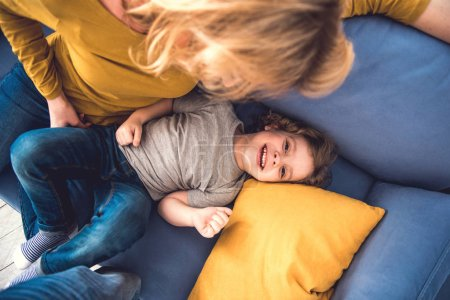 Smiling little boy is having fun with mom at home