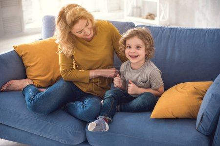 Cheerful mummy is fondling her laughing son in lounge room