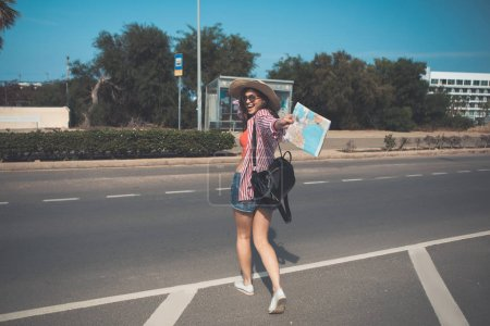Photo for Lets begin journey. Portrait of excited girl is showing map and smiling. She is going to bus stop with joy - Royalty Free Image