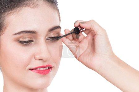 Photo pour Styliste en appliquant le mascara sur les cils avec pinceau de maquillage de la belle femme - image libre de droit