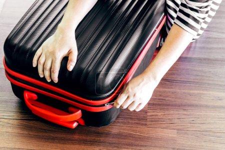 Photo pour Femme emballant un bagage sur le sol en bois - image libre de droit
