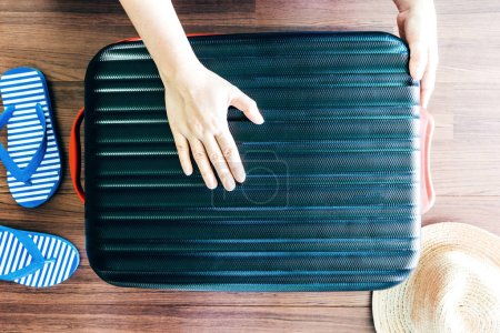 Photo for Woman packing a luggage on wooden floor - Royalty Free Image