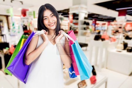 Photo for Happy woman holding shopping bags at shopping mall - Royalty Free Image