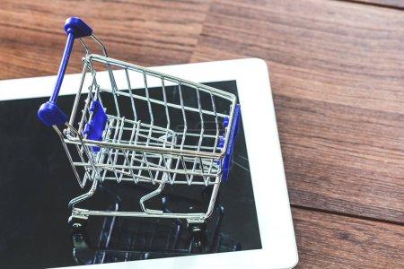 Photo pour Panier d'achat et de la tablette sur une table en bois - concept de magasinage en ligne - image libre de droit