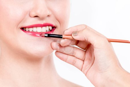 Photo pour Styliste, application de brillant à lèvres rouges à la belle femme - image libre de droit