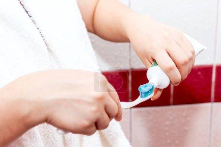 Photo pour Femme appliquant du dentifrice sur la brosse à dents dans la salle de bain - image libre de droit