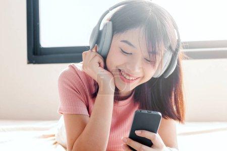 Photo pour Femme écoutant de la musique avec écouteurs sur le lit - image libre de droit