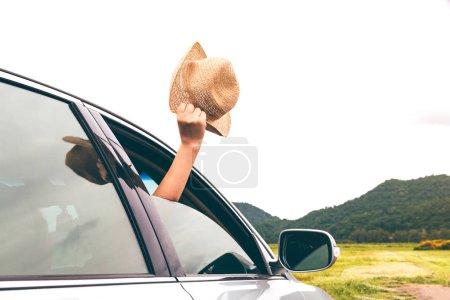 Photo pour Main de femme tenant le chapeau sur le voyageur détente et plaisir en voiture avec fond de montagne - image libre de droit