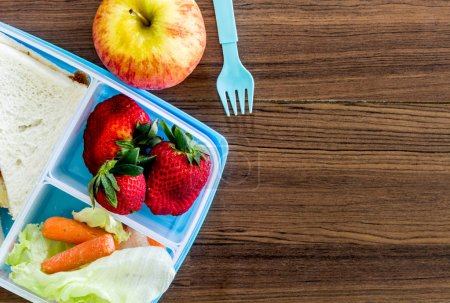 Photo for Lunch box with vegetables and slice of bread for a healthy school lunch on wooden table - Royalty Free Image