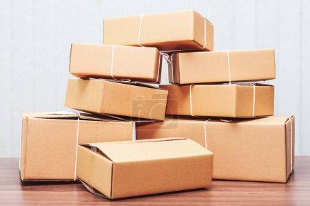 Photo pour Empilement de boîtes en carton sur table en bois - image libre de droit