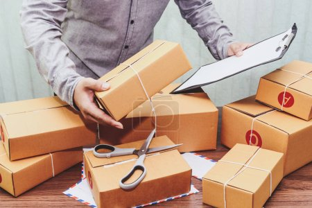 Photo for Delivery man holding clipboard and cardboard box for for delivery - Royalty Free Image