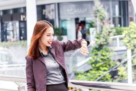 Photo for Business woman looking at watch at office building - Royalty Free Image