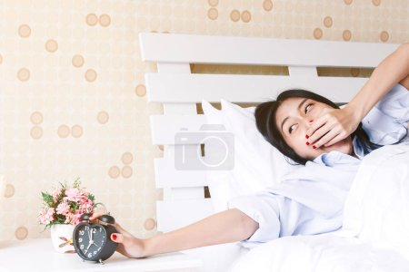 Photo pour Femme tenant le réveil sur le lit le matin - image libre de droit