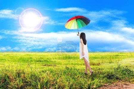 Photo pour Femme tenant parapluie coloré sur herbe verte avec ciel bleu - image libre de droit