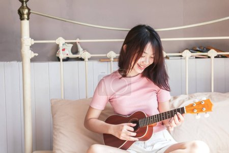Photo for Woman playing a guitar on bed - Royalty Free Image