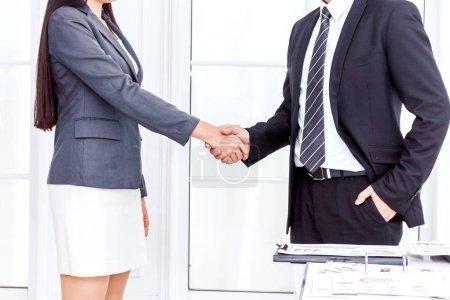 Photo pour Deux partenaires commerciaux se serrant la main au bureau - image libre de droit