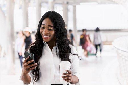 Photo pour Femme afro-américaine avec café et smartphone - image libre de droit