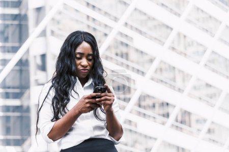 Photo pour Femme afro-américaine utilisation smartphone - image libre de droit
