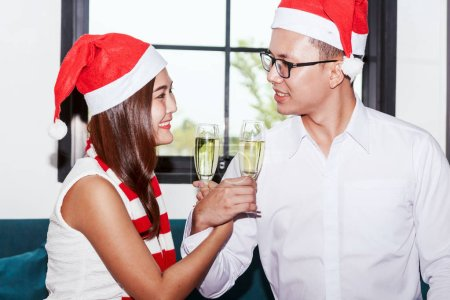 Photo for Young couple celebrating and holding glasses of champagne at home - Royalty Free Image