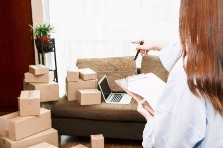 Photo pour Liste de contrôle jeune femme avec boîte en carton à la maison - Business en ligne et concept de livraison - image libre de droit