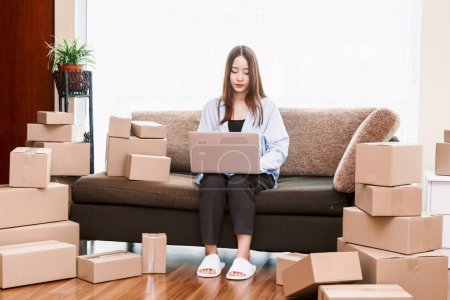 Photo for Young woman holding laptop with cardboard box at home - Business online and delivery concept - Royalty Free Image